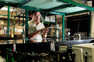 Hui Zhao, assistant professor of physics and astronomy at Kansas, goes over an experiment.
