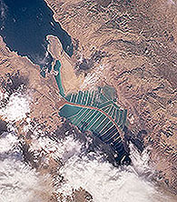 Satellite image of the southern basin of the Dead Sea, with the APC salt ponds on the right and the Israeli salt ponds on the left, separated by a central canal that is also the international border between the two countries.