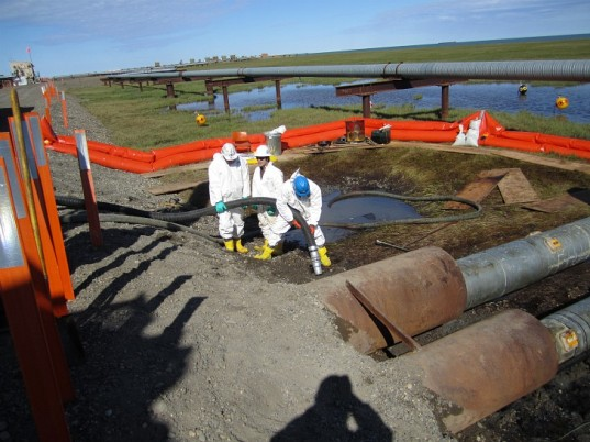 Workers suck up parts of the spill in Alaska.