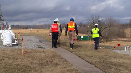 Workers investigate a pipeline oil spill that leaked thousands of gallons of crude oil near Everton, MO.